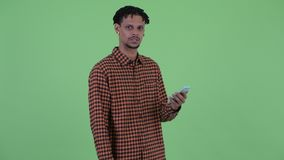 Stressed young African man using phone and getting bad news. Studio shot of young handsome African man with dreadlocks against chroma key with green background stock video footage