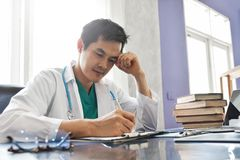 Stressed Young Asian male doctor is working. Stressed Young Asian male doctor is working in a medical room at a hospital royalty free stock images