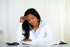 Stressed young black woman reading a book Royalty Free Stock Image