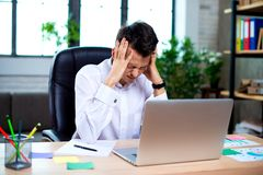 Stressed young businessman shocked by bad news using laptop at work, desperate bankrupt investor lost money, financial problem. Debt, tired of overwork stock photo