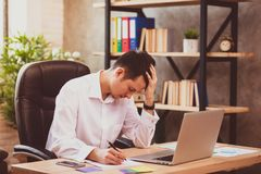 Stressed young businessman shocked by bad news using laptop at work, desperate bankrupt investor lost money, financial problem. Debt, tired of overwork royalty free stock photo