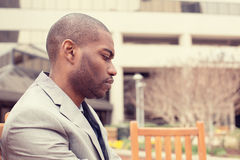 Stressed young businessman sitting outside corporate office looking down Royalty Free Stock Photo