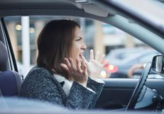 Stressed young businesswoman driving her car. In the city. She is nervous and angry Royalty Free Stock Images