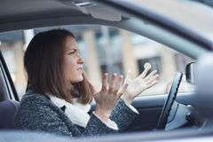 Stressed young businesswoman driving her car. In the city. She is nervous and angry Stock Images