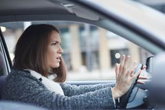 Stressed young businesswoman driving her car. In the city. She is nervous and angry Royalty Free Stock Photos