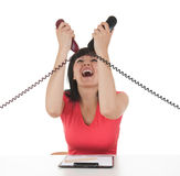 Stressed young businesswoman with phones Stock Photography