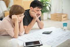 Stressed Young couple calculating their budget. For new house stock photography