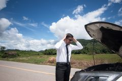 Stressed young man with broken car in the middle . Royalty Free Stock Image