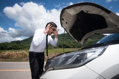 Stressed young man with broken car in the middle at the countrys Royalty Free Stock Images