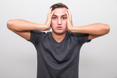 Stressed young man covers ears by hands and shouting Stock Photography