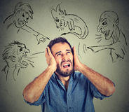 Stressed young man covers his ears with his hands evil guys pointing fingers at him Royalty Free Stock Photos