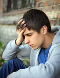 Stressed Young Man outdoor. Sad Young Man sit on the Brick Wall Background royalty free stock photography
