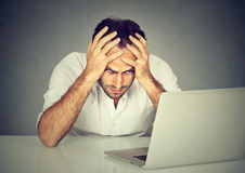 Stressed young man sitting at his desk in front of computer Stock Photos