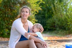 Stressed young mother comforting her crying son. Stressed young mother comforting her crying baby son looking away with an anguished expression as they sit stock image