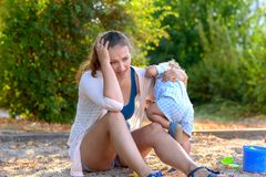 Stressed young mother with a difficult baby boy. Staring dejectedly at the ground in a playground as the infant acts up royalty free stock images