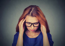 Stressed young redhead business woman having headache stock photo