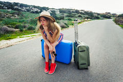 Stressed young tourist woman sitting on suitcases Royalty Free Stock Photo