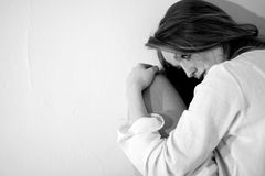 Stressed young woman. Young woman withdrawn and showing stress; black and white photo Royalty Free Stock Photography