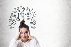 Stressed young woman with a bun, question marks. Stressed out young woman wearing a white sweater and holding her head with both hands. Concrete wall background Royalty Free Stock Image