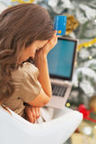 Stressed young woman with credit card and laptop. In front of christmas tree Stock Images