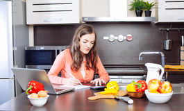 Stressed young woman is doing banking and administrative work ho Royalty Free Stock Images