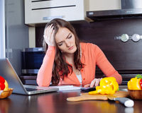 Stressed young woman is doing banking and administrative work ho Stock Photo