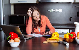 Stressed young woman is doing banking and administrative work ho Royalty Free Stock Photography