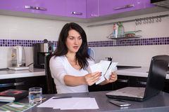Stressed young woman. Is doing banking and administrative work holding bills at home Royalty Free Stock Images