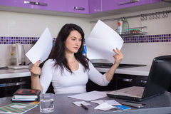 Stressed young woman. Is doing banking and administrative work holding bills at home Stock Photos