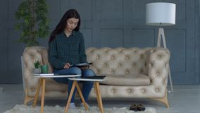 Stressed young woman doing home accouting on sofa stock video footage
