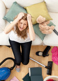Stressed young woman doing housework. In the living-room Royalty Free Stock Photography