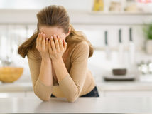 Stressed young woman in kitchen Royalty Free Stock Images