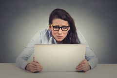 Stressed young woman looking at computer Royalty Free Stock Image