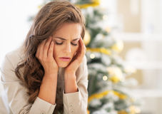 Stressed young woman near christmas tree. Portrait of stressed young woman near christmas tree Stock Images