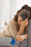 Stressed young woman with phone and credit card Stock Images