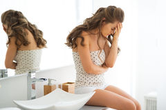 Stressed young woman sitting in bathroom Stock Photography