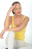 Stressed Young Woman Sitting on the Floor Rubbing Her Forehead Royalty Free Stock Images