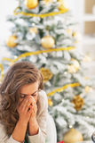 Stressed young woman sitting in front of christmas tree Stock Photo