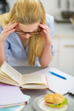 Stressed young woman studying in kitchen Royalty Free Stock Images