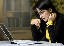 Stressful bills to pay. A brunette woman sitting at the living room table, looking with concern at her monthly bills to pay. Laptop computer used to pay online Royalty Free Stock Images