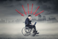 Stressful businessman with wheelchair and arrow Royalty Free Stock Photo