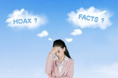 Stressful businesswoman with hoax or fact stock photography