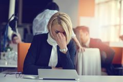 Feeling tired and stressed. Frustrated adult woman keeping eyes closed from fatigue while sitting in office. Stressful day. Feeling tired and stressed royalty free stock images