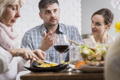 Stressful dinner with parents-in-law. Young men and two women sitting beside table during family dinner Royalty Free Stock Photos