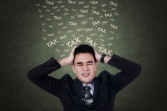 Stressful entrepreneur with taxes text Royalty Free Stock Photo