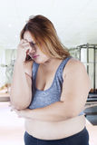 Stressful fat woman in fitness center. Portrait of overweight woman standing in the fitness center and looks stressful Royalty Free Stock Images