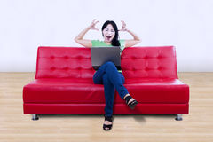 Stressful female with laptop sit on red sofa Royalty Free Stock Images