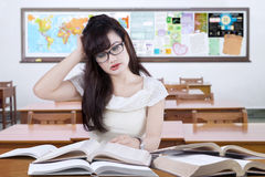 Stressful female learner studying in the classroom Royalty Free Stock Photo