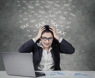 Stressful female worker paying her tax Royalty Free Stock Photos