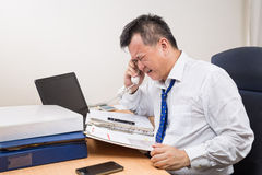 Stressful and frustrated Asian manager talking on telephone in o. Busy, stressful and frustrated Asian business manager talking on telephone in office Royalty Free Stock Image